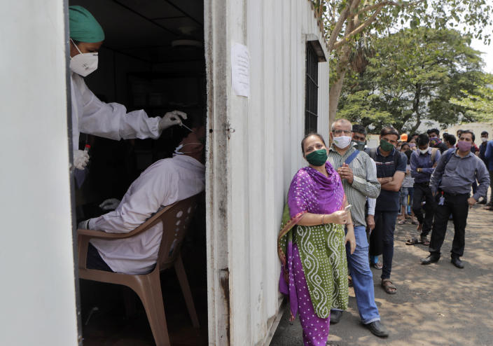 A health worker takes a nasal swab sample of a person to test for COVID-19 as others wait for their turn outside a field hospital in Mumbai, India, Thursday, May 6, 2021. Infections in India hit another grim daily record on Thursday as demand for medical oxygen jumped seven-fold and the government denied reports that it was slow in distributing life-saving supplies from abroad. (AP Photo/Rajanish kakade)