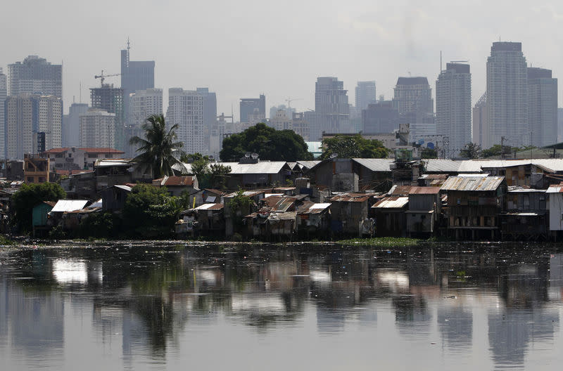 High-rise buildings are seen in the background with slum dwellings in the front, near a polluted river in Manila