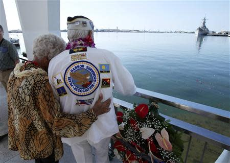 Pearl Harbor survivor Dalton Walling and his fiance Joan Pohl look down at the sunken USS Arizona and the USS Missouri in the background while on board the USS Arizona Memorial during the 72nd anniversary of the attack on Pearl Harbor at the WW II Valor in the Pacific National Monument in Honolulu, Hawaii on December 7, 2013. REUTERS/Hugh Gentry