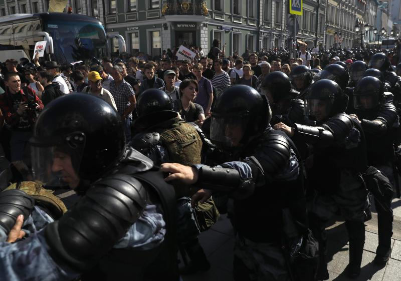 Police block a street during an unsanctioned rally in the center of Moscow, Russia, Saturday, July 27, 2019. Russian police clashed with demonstrators and have arrested some hundreds in central Moscow during a protest demanding that opposition candidates be allowed to run for the Moscow city council. (AP Photo/ Pavel Golovkin)