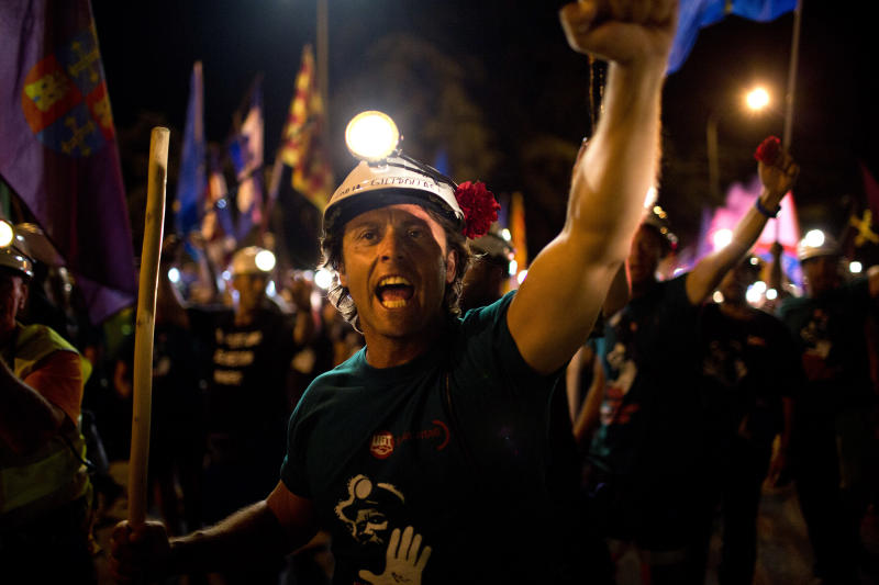 Miners sing as they march along a street after walking for more than 20 days from the northern Asturias and Leon regions, as many as 400 kilometers (250 miles), on their way to Puerta del Sol, the Spanish capital's most emblematic square in Madrid, Spain Tuesday, July 10, 2012. Spanish coal miners angered by huge cuts in government subsidies for their industry converged on Madrid Tuesday for protest rallies after walking nearly three weeks under a blazing sun from the pits where they eke out a living. (AP Photo/Emilio Morenatti)