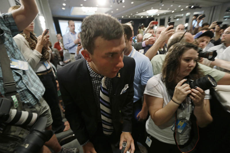 Texas A&M quarterback Johnny Manziel fights his way through a crowd of photographers and reporters as he arrives for the Southeastern Conference football Media Days in Hoover, Ala., Wednesday, July 17, 2013. (AP Photo/Dave Martin)
