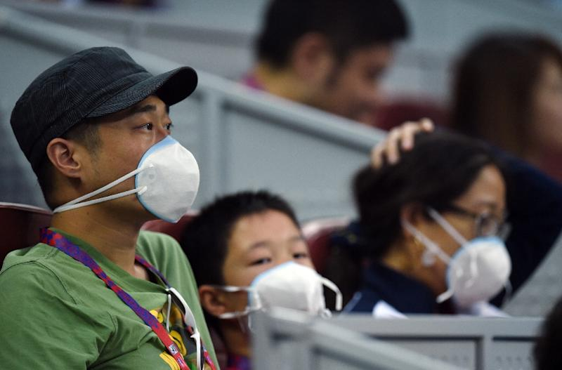 Spectators wear face masks as they watch a match at the China Open tennis tournament in Beijing on October 5, 2015 (AFP Photo/Greg Baker)