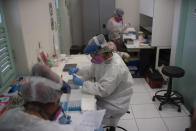 Researchers work in a state-run Fiocruz Institute laboratory at Pedra Branca state park, near Rio de Janeiro, Brazil, Tuesday, Oct. 29, 2020. Their goal is to identify other viruses that may be highly contagious and lethal in humans, and to use that information to devise plans to stop them from ever infecting people. (AP Photo/Silvia Izquierdo)