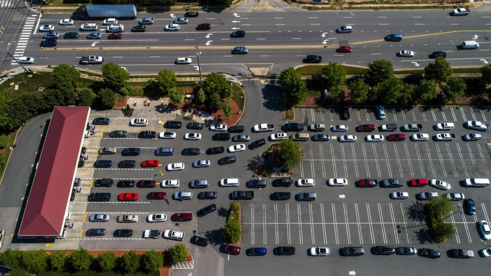 Vehicles wait in lines at the Costco in Raleigh, N.C., Thursday, May 13, 2021. Operators of the Colonial Pipeline say they began the process of moving fuel through the pipeline again on Wednesday, six days after it was shut down because of a cyberattack. (Travis Long/The News & Observer via AP)