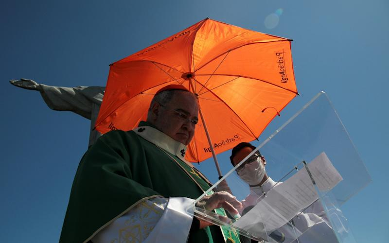 An acolyte holds an umbrella over Rio de Janeiro's Archbishop Orani Tempesta to protect him from the sun as he leads a mass in tribute to the victims of the coronavirus  - REUTERS/Ian Cheibub
