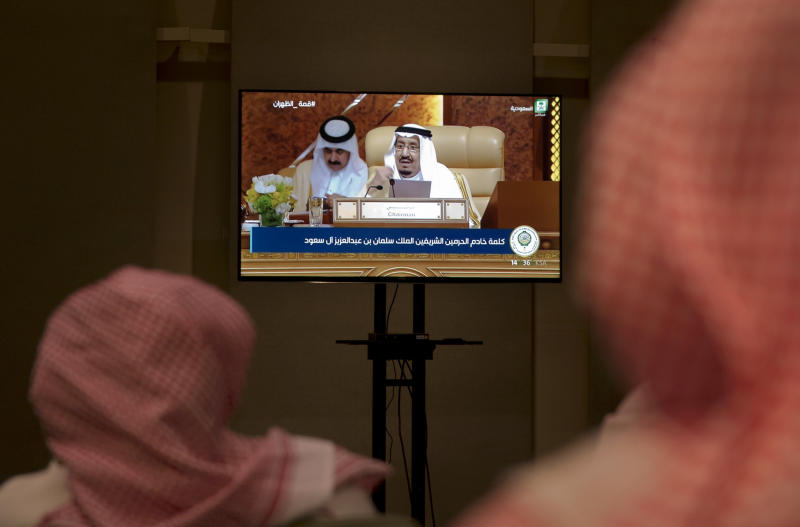 Reporters watch the speech of Saudi King Salman from a press room, during the opening of the Arab summit in Dhahran, Saudi Arabia, Sunday, April 15, 2018. The summit opened in the eastern Saudi city of Dhahran as tensions with Iran and wars in Syria and Yemen threaten stability across the region. Salman told leaders from across the 22-member Arab League that Iran was to blame for instability and meddling in the region. (AP Photo/Amr Nabil)