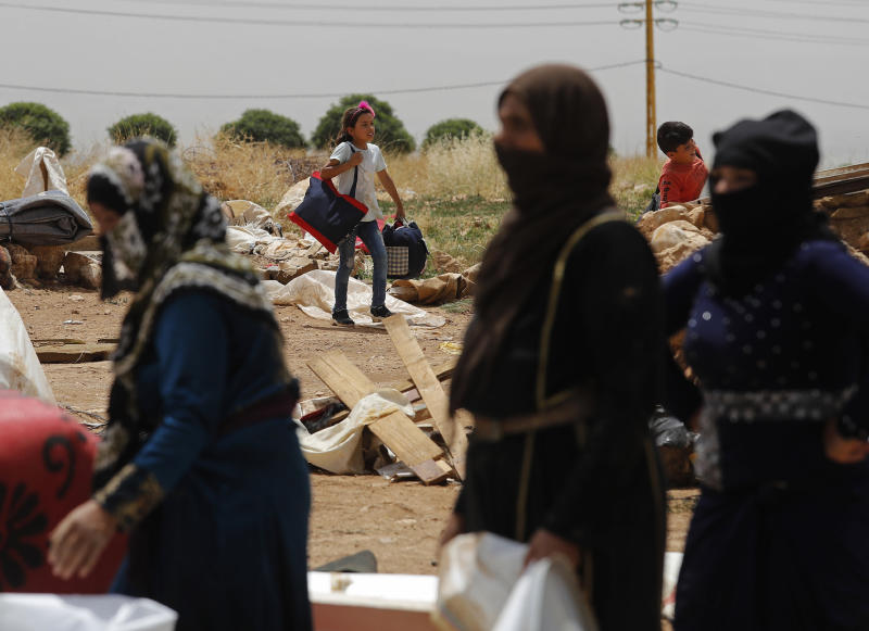 A Syrian girl, center, carries her belongings as she evacuates an informal refugee camp after a fight broke out last week between camp residents and Lebanese firefighters who arrived to put out a fire, in Deir Al-Ahmar, east Lebanon, Sunday, June 9, 2019. Dozens of Syrian refugees have dismantled their tents in a camp they lived in for years in eastern Lebanon after authorities ordered their evacuation following a brawl with locals. Lebanon hosts over 1 million Syrian refugees who fled the war next door since 2011, overwhelming the country of nearly 5 million. (AP Photo/Hussein Malla)