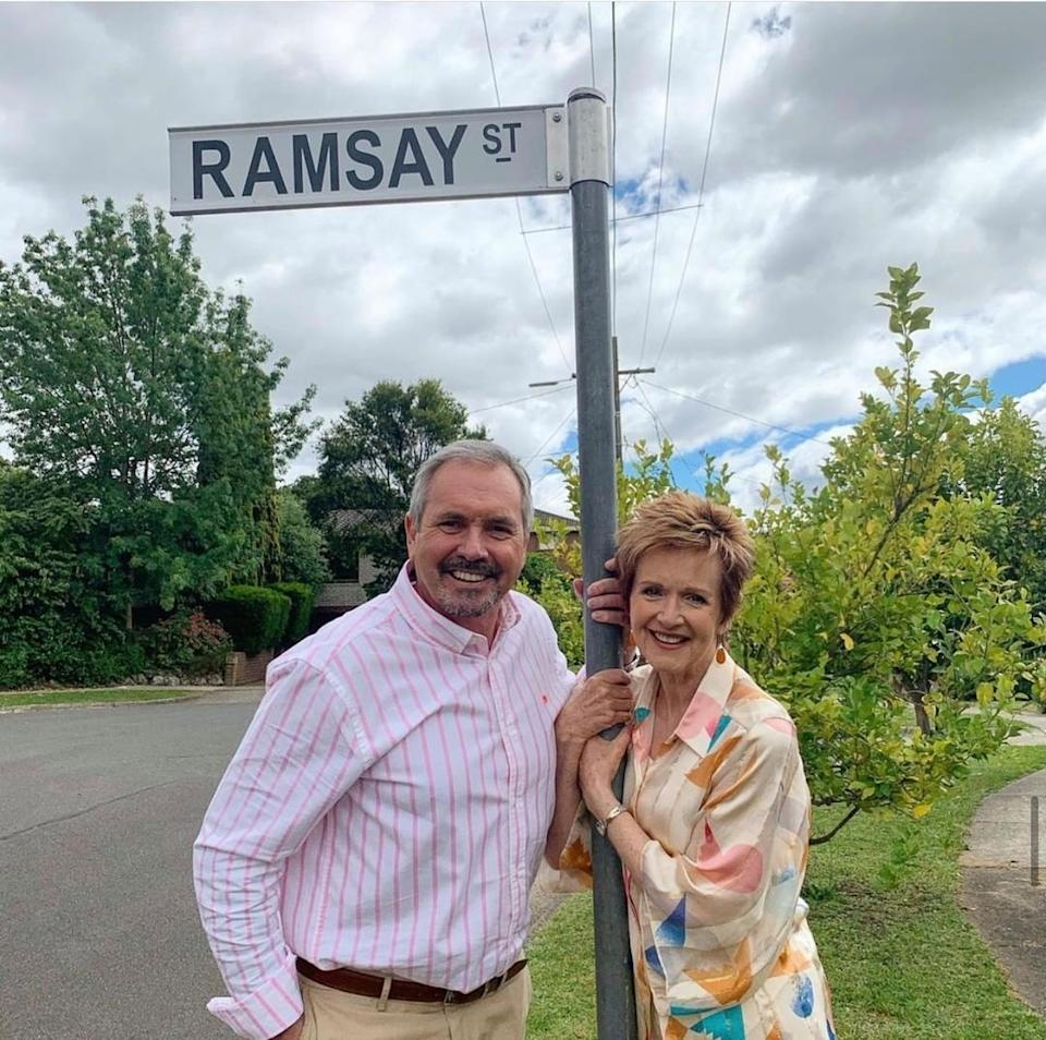 Neighbours stars in front of Ramsay St sign.