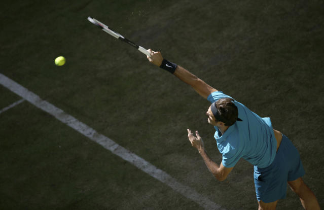 Switzerland Roger Federer returns a ball to France's Benoit Paire in their round of 16 match at the ATP tennis tournament in Halle, western Germany, Thursday, June 21, 2018. (Friso Gentsch/dpa via AP)