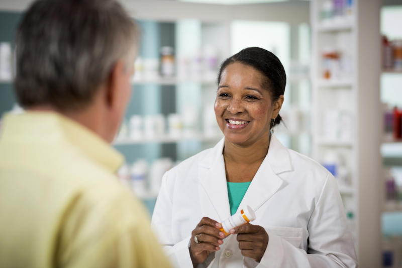 A pharmacist holding a prescription bottle while speaking with a customer.