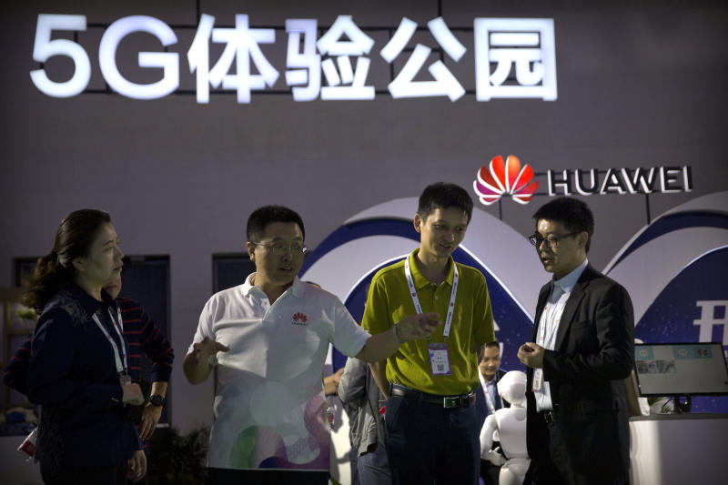 FILE - In this Sept. 26, 2018, file photo, visitors look at a display for 5G wireless technology from Chinese technology firm Huawei at the PT Expo in Beijing. While a Huawei executive faces possible U.S. charges over trade with Iran, the Chinese tech giant's ambition to be a leader in next-generation telecoms is colliding with security worries abroad. (AP Photo/Mark Schiefelbein, File)