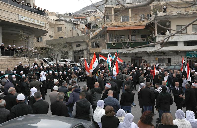Druze residents on the Israeli-occupied Golan Heights wave Syrian and Druze flags as they protest against US President Donald Trump's pledge to recognise Israeli sovereignty over the strategic plateau on March 23, 2019