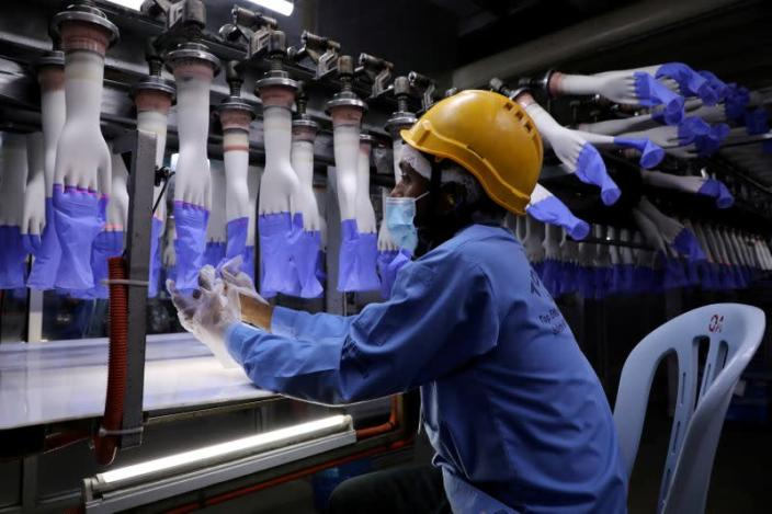 FILE PHOTO: A worker inspects newly-made gloves at Top Glove factory in Shah Alam