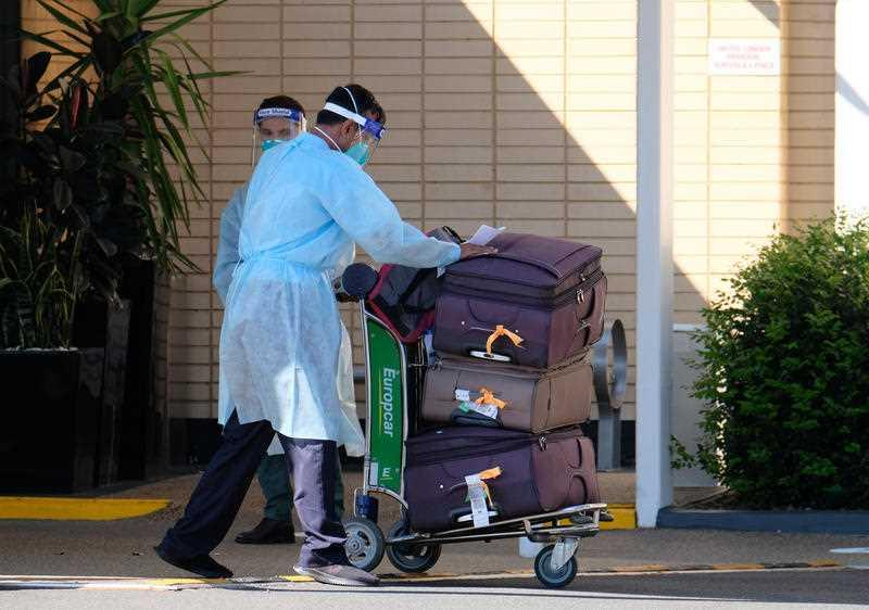 Pictured are two people wearing PPE moving suitcases in Melbourne.