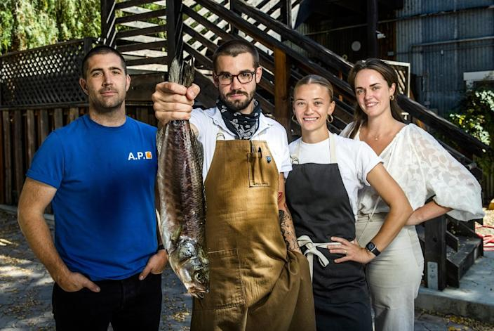Two men, one holding a large fish by its tail, and two women stand outside Bar Le Côte.
