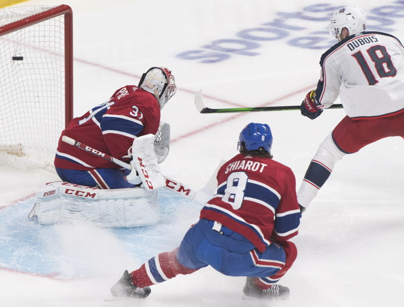 Columbus Blue Jackets' Pierre-Luc Dubois scores against Montreal Canadiens goaltender Carey Price as Canadiens' Ben Chiarot defends during second-period NHL hockey game action in Montreal, Sunday, Feb. 2, 2020. (Graham Hughes/The Canadian Press via AP)