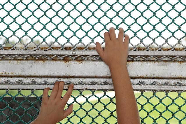 A Cuban girl waits with her asylum-seeking family on the Mexican side of the Brownsville-Matamoros International Bridge near Brownsville, Texas, on July 2. The family had been denied entry into the U.S. (Photo: Loren Elliott/Reuters)
