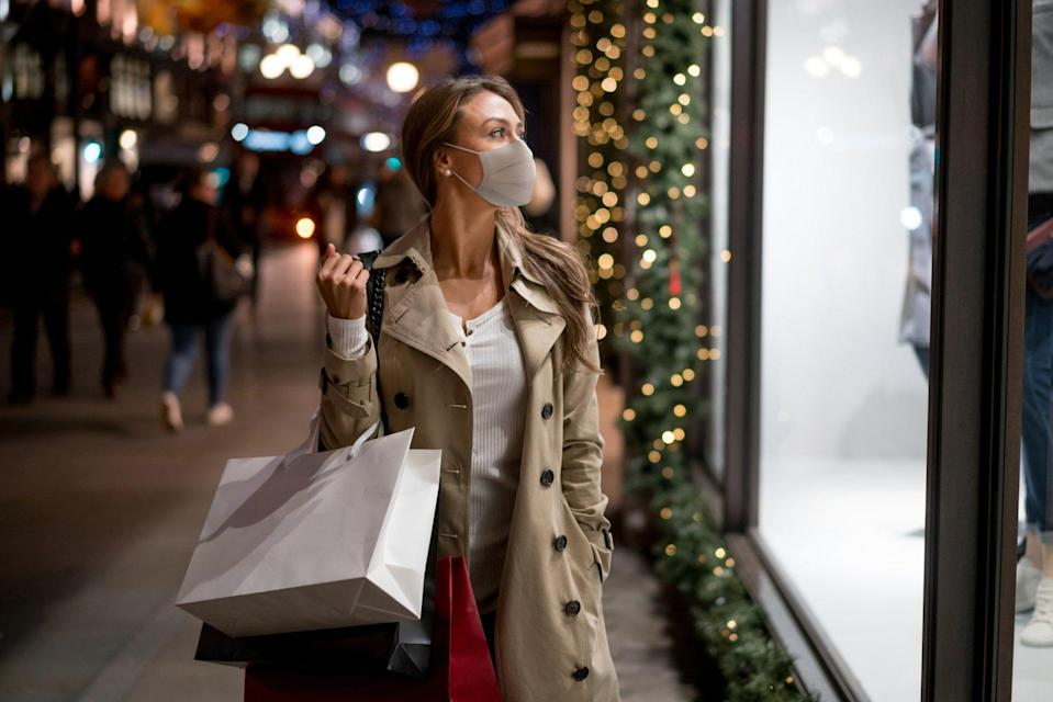Happy woman Christmas shopping wearing a facemask and looking at a window carrying bags.