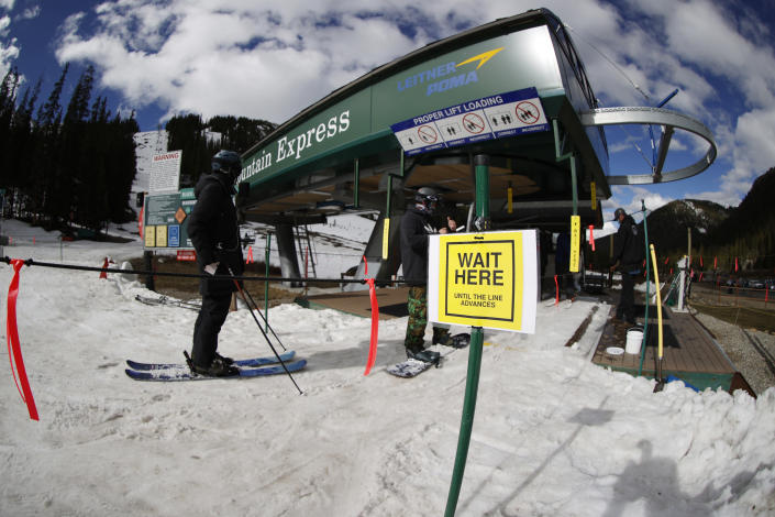 FILE - In this May 27, 2020, file photo, a sign reminds skiers to wait at socially-distant intervals before getting on a lift at the reopening of Arapahoe Basin Ski Resort, which closed in mid-March to help in the effort to stop the spread of the new coronavirus, in Keystone, Colo. The virus has created a number of new wrinkles for skiers and snowboarders to navigate as the winter sports season opens. (AP Photo/David Zalubowski, File)