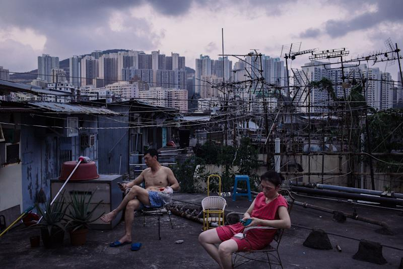 Migrant workers take a break after dinner outside a rooftop hut on June 3, 2017, in Hong Kong. Inequality has been on the rise for years, causing experts to worry about its destabilizing effects.