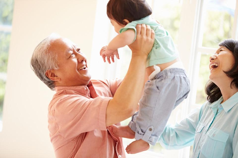 asian grandfather holding grandchild while grandmother looks on