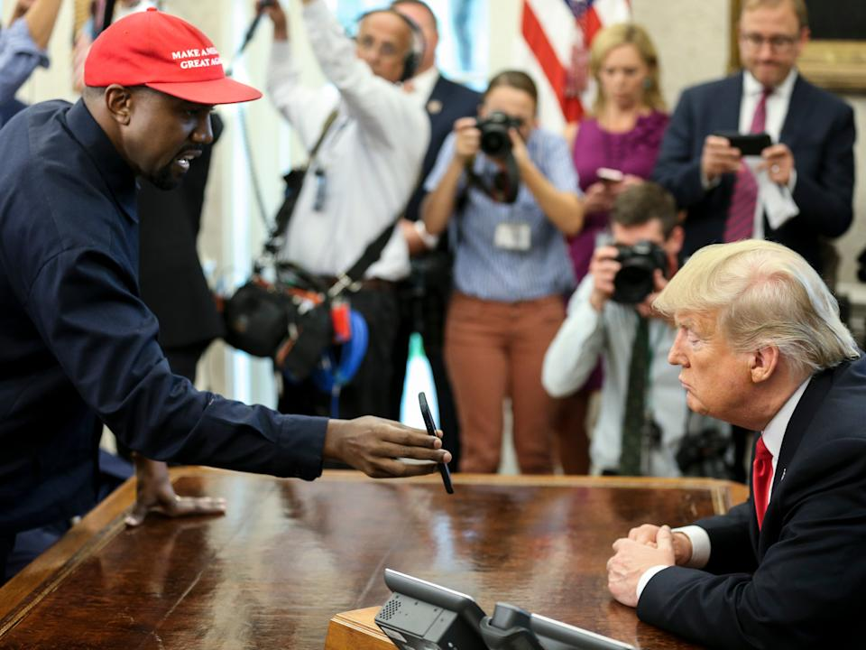 Kanye West shows a picture on a phone to Donald Trump during a meeting in the Oval Office, 11 October, 2018Getty Images