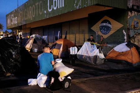 FILE PHOTO: Venezuelan men erect their tent to sleep as they wait to show their passports or identity cards next day at the Pacaraima border control, Roraima state, Brazil August 8, 2018. Picture taken August 8, 2018. REUTERS/Nacho Doce
