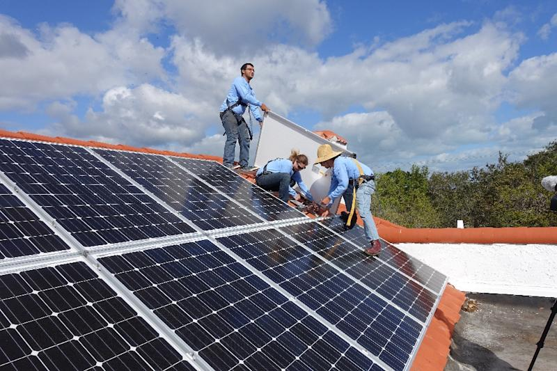 Workers install solar panels on a rooftop on February 20, 2015 at a home in Palmetto Bay, Florida (AFP Photo/Kerry Sheridan)