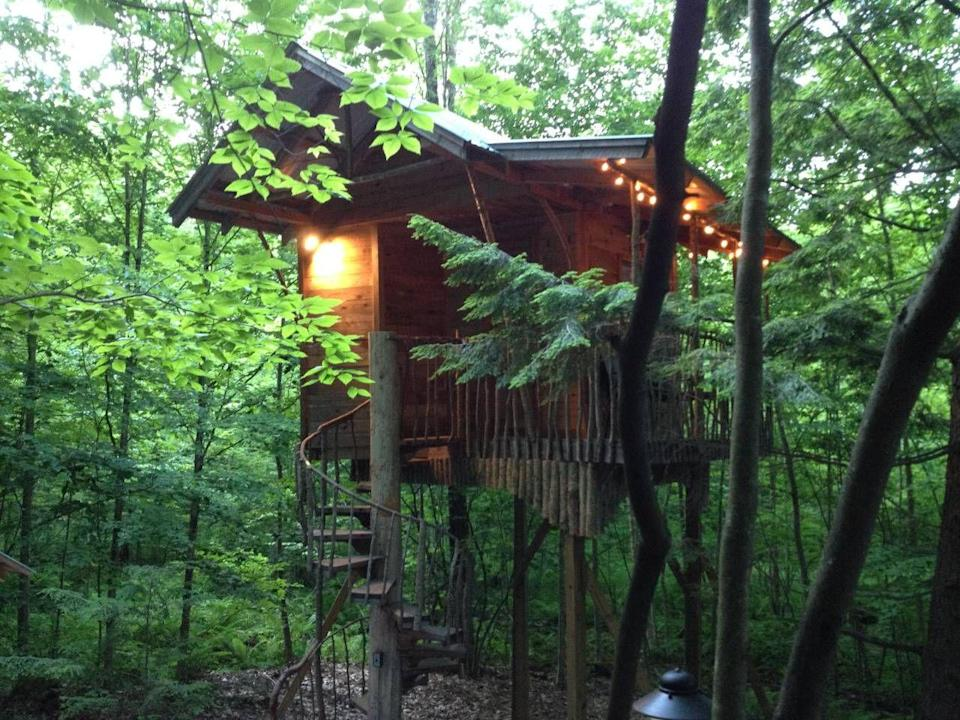 """<p>In the woods of Middle Grove, New York, visitors can climb a winding staircase to this cozy, treetop cabin. It's outfitted with an outdoor kitchen, full bath, fire pit, and deck that's ideal for overlooking the surrounding greenery.</p><p><a class=""""link rapid-noclick-resp"""" href=""""https://www.airbnb.com/rooms/2403570"""" rel=""""nofollow noopener"""" target=""""_blank"""" data-ylk=""""slk:BOOK NOW"""">BOOK NOW</a> <strong><em>Adirondack Treehouse Retreat</em></strong><br></p>"""