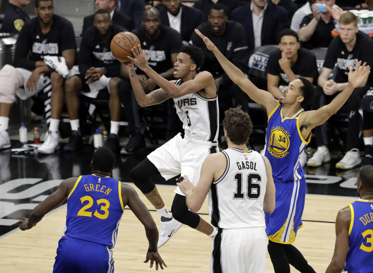 San Antonio Spurs guard Dejounte Murray (5) leaps to the basket for a shot as Golden State Warriors' Draymond Green (23) and Shaun Livingston (34) defend during the first half in Game 4 of the NBA basketball Western Conference finals, Monday, May 22, 2017, in San Antonio. The Spurs' Pau Gasol (16) watches on the play. (AP Photo/Eric Gay)