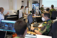Rear Admiral Henrique Gouveia e Melo, background right, chairs the daily briefing of the COVID-19 vaccination task force at their headquarters in Oeiras, outside Lisbon, Thursday, Sept. 16, 2021. As Portugal nears its goal of fully vaccinating 85% of the population against COVID-19 in nine months, other countries want to know how it was able to accomplish the feat. A lot of the credit is going to Gouveia e Melo. (AP Photo/Armando Franca)