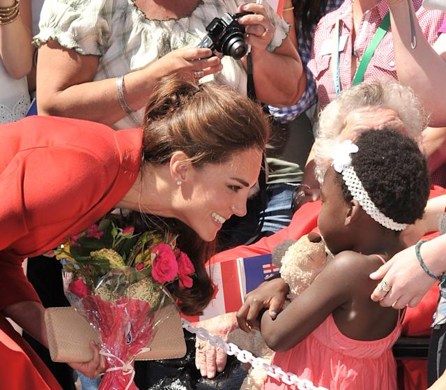 <p>Catherine, Duchess of Cambridge, receives a bouquet of flowers from a young girl in Calgary, Canada. (Photo by George Pimentel/WireImage) </p>