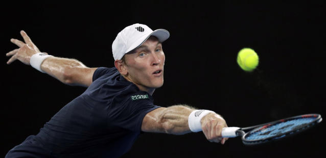 United States' Mitchell Krueger reaches for a backhand return to Serbia's Novak Djokovic during their first round match at the Australian Open tennis championships in Melbourne, Australia, Tuesday, Jan. 15, 2019. (AP Photo/Kin Cheung)