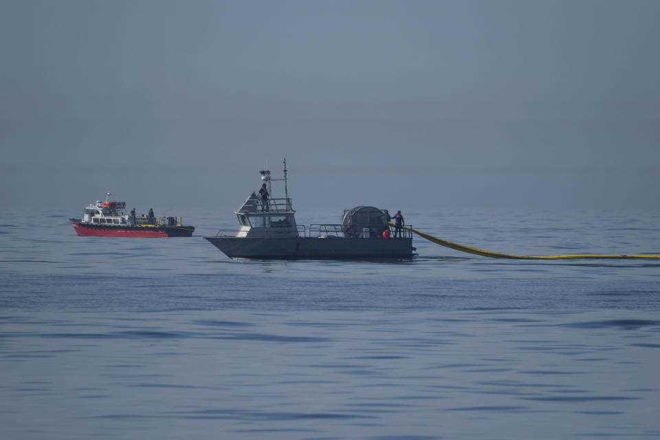 A Marine Spill Response Corporation (MSRC) vessel, foreground, an oil spill removal organization (OSRO), deploys floating barriers known as booms to try to stop further incursion of an oil slick off Huntington Beach, Calif., Sunday, Oct. 3, 2021. (AP Photo/Ringo H.W. Chiu)