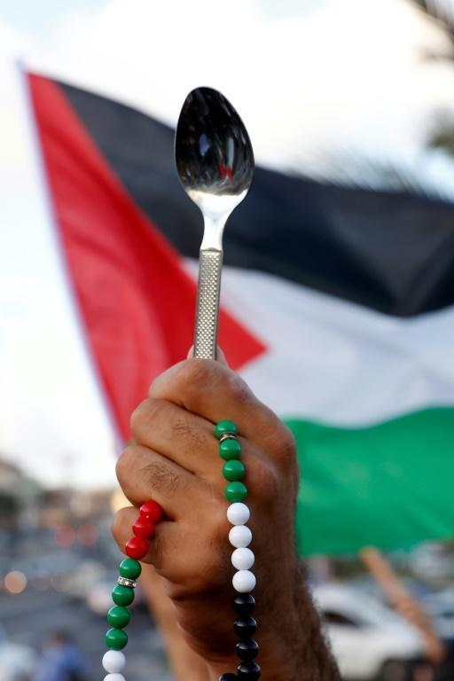 Arab Israeli protesters lift spoons during a demonstration in the mostly Arab city of Umm al-Fahm in northern Israel in September 2021 (AFP/JACK GUEZ)