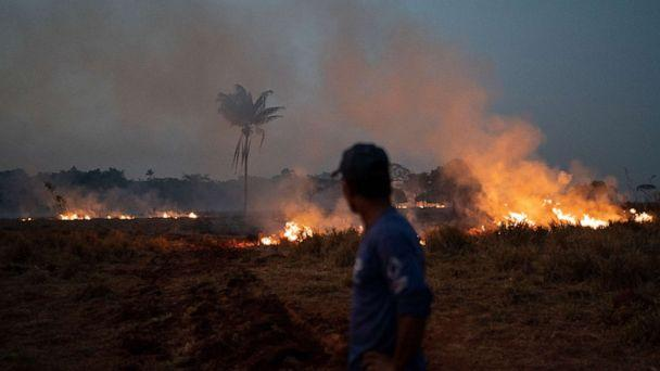 PHOTO: Neri dos Santos Silva watches an encroaching fire threat after digging trenches to keep the flames from spreading to the farm he works on, in the Nova Santa Helena municipality, in the state of Mato Grosso, Brazil, Friday, Aug. 23, 2019. (Leo Correa/AP)