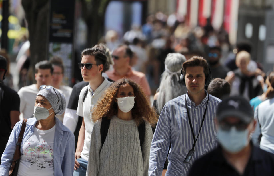 Shoppers wear face masks to protect themselves from COVID-19 as they walk along Oxford Street in London, Friday, July 24, 2020. New rules on wearing masks in England have come into force, with people going to shops, banks and supermarkets now required to wear face coverings. Police can hand out fines of 100 pounds ($127) if people refuse, but authorities are hoping that peer pressure will prompt compliance. (AP Photo/Frank Augstein)