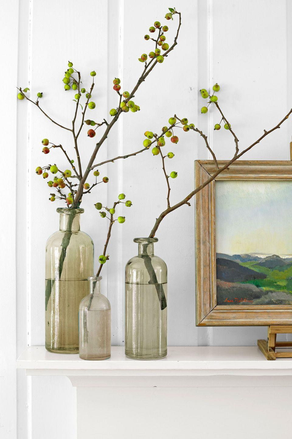 """<p>The best thing about this sort of display? There's absolutely no arranging involved. Liza Lubell of <a href=""""http://peartreeflowers.com"""" rel=""""nofollow noopener"""" target=""""_blank"""" data-ylk=""""slk:Brooklyn's Peartree Flowers"""" class=""""link rapid-noclick-resp"""">Brooklyn's Peartree Flowers</a> simply stripped the leaves from each limb before putting it in a vase. """"This treatment highlights the prettiest feature of the plant—its fruit,"""" she explains. Group several different-size vases for even greater visual payoff. </p>"""