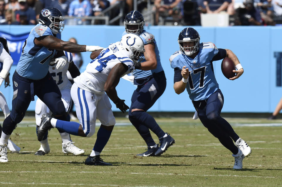 Tennessee Titans quarterback Ryan Tannehill (17) scrambles past Indianapolis Colts defensive end Tyquan Lewis (94) in the first half of an NFL football game Sunday, Sept. 26, 2021, in Nashville, Tenn. (AP Photo/Mark Zaleski)