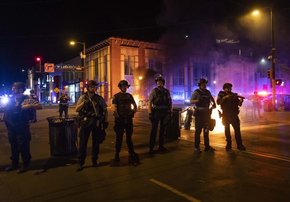 Police stand guard after protesters set fire to dumpsters on the street after a vigil was held for Winston Boogie Smith Jr. early on Saturday, June 5, 2021. Smith was shot and killed by law enforcement officers on Thursday during an arrest warrant operation. (AP Photo/Christian Monterrosa)