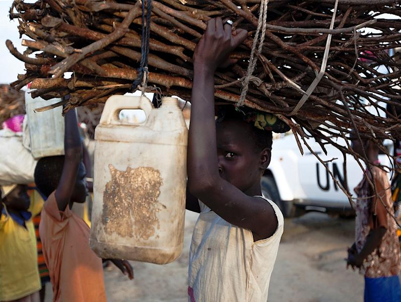 A young woman carries firewood after returning to the United Nations base outside Bentiu (AFP Photo/Tristan McConnell)