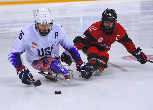 USA's Declan Farmer (L) and Canada's Greg Westlake (R) fight for the puck in the ice hockey gold medal game (AFP Photo/Jung Yeon-je)