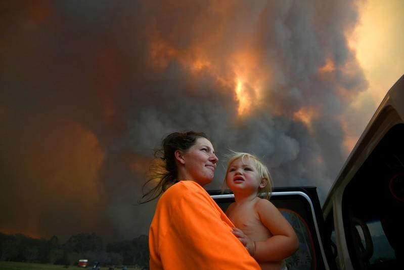 Sharnie Moren and her 18-month-old daughter Charlotte look on as thick smoke rises from bushfires near Nana Glen