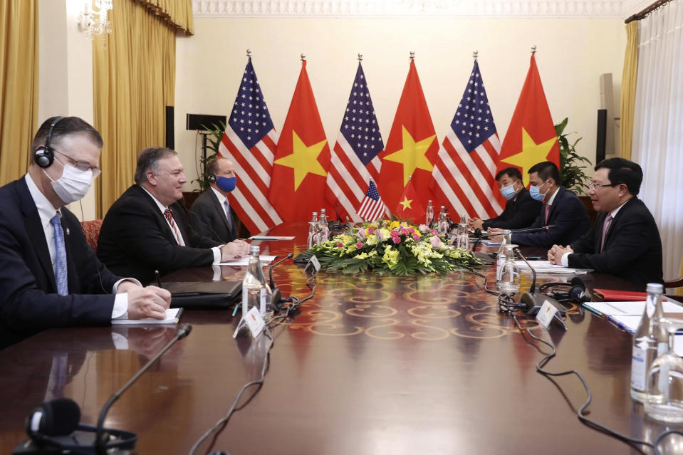 U.S. Secretary of State Mike Pompeo, second from left, and Vietnamese Foreign Minister Pham Binh Minh, right, attend a meeting in Hanoi, Vietnam, Friday, Oct. 30, 2020. Pompeo is wrapping up an anti-China tour of Asia in Vietnam as the fierce American presidential election race enters its final stretch. (Bui Lam Khanh/VNA via AP)