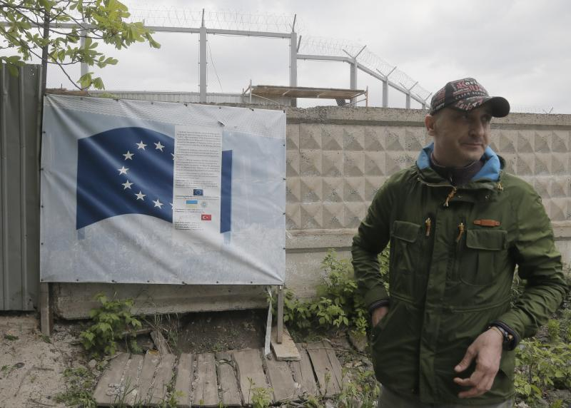 """In this photo taken Tuesday, April 29, 2014, deputy head of the construction site, Volodymyr Pashchenko, supervises work on the construction of a detention center in Zhdanivka, near Donetsk, Ukraine. Moscow calls the detention center under construction near the Russian border a """"fascist concentration camp."""" Inside the barbed-wire fences, the reality is less ominous: It's an EU-funded project to hold asylum seekers and illegal immigrants, similar to countless detention centers across Europe. (AP Photo/Efrem Lukatsky)"""