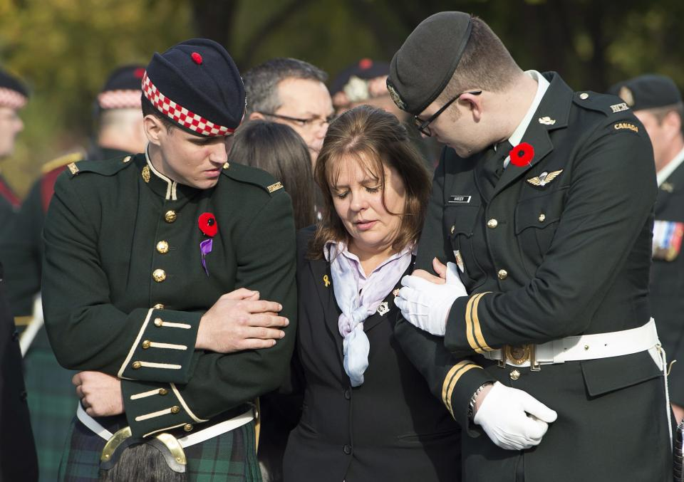 Kathy Cirillo is conforted by soldiers during the funeral procession for her son Cpl. Nathan Cirillo in Hamilton, Ontario, on Tuesday, Oct. 28, 2014. Cirillo was standing guard at the National War Memorial in Ottawa last Wednesday when he was killed by a gunman who went on to open fire on Parliament Hill before being shot down in a hail of bullets. (AP Photo/The Canadian Press, Frank Gunn)