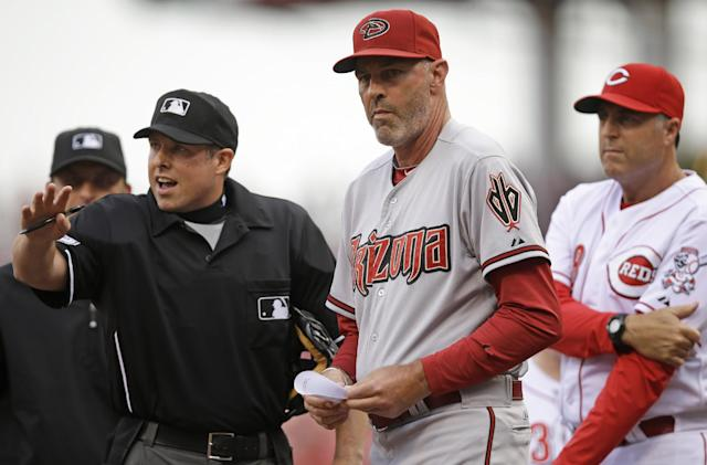 Arizona Diamondbacks manager Kirk Gibson, center, and Cincinnati Reds manager Bryan Price, right, listen to home plate umpire Hal Gibson go over the ground rules prior to a baseball game, Monday, July 28, 2014, in Cincinnati. (AP Photo/Al Behrman)