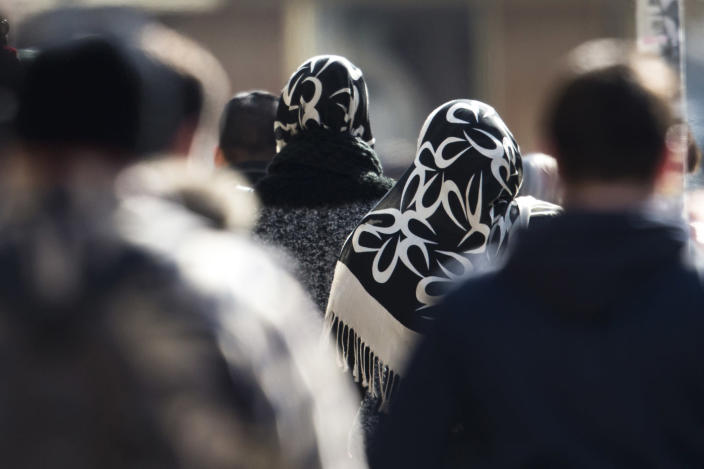 In this picture taken March 15, 2013 women with headscarfs, a traditional dress for islamic women, walk between other people on a street at the district Neukoelln in Berlin, Friday, March 15, 2013. (AP Photo/Markus Schreiber)