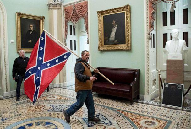 PHOTO: A supporter of President Donald Trump that breeched security and entered the U.S. Capitol in protest, carries the Confederate flag, Jan. 6, 2021, in Washington, D.C. (Saul Loeb/AFP via Getty Images)
